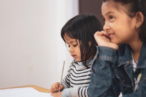 Irmãs escrevendo em papel branco