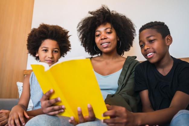 mãe lendo para seus dois filhos