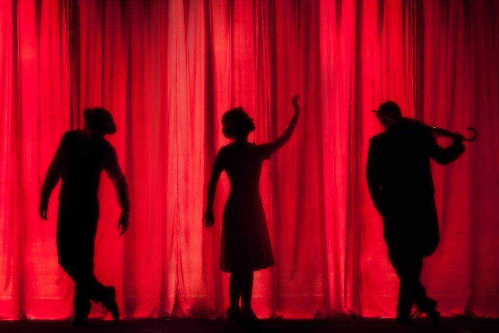 Imagem de três pessoas em cena no palco, exercitando suas inteligências múltiplas.