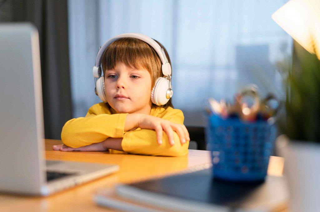 Criança assiste aulas a distância pelo computador.