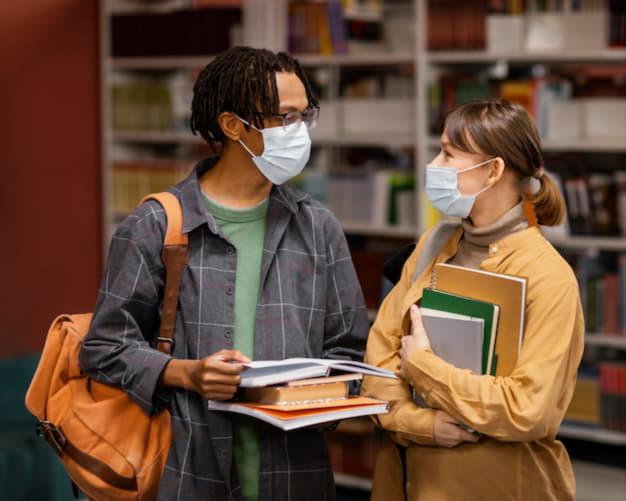 Dois adolescentes conversam com livros nas mãos. Os itinerários formativos promovem a eles experiências variadas.