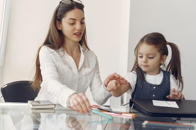Mulher ajuda criança nas tarefas de alfabetização e letramento na Educação Infantil.