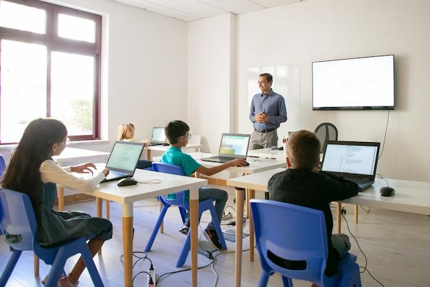 Um professor a frente da sala de aula com quatro crianças utilizando seus computadores. A gestão democrática na escola traz benefícios para todos.