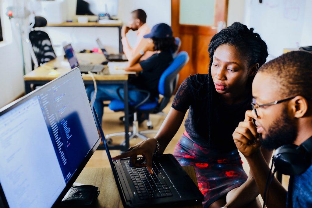 Dois colaboradores da gestão administrativa escola, um homem e uma mulher, verificando as manutenções em um computador.