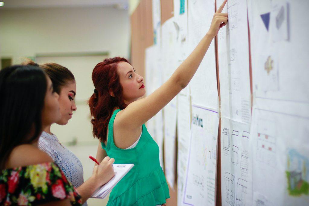 Professora apontando no quadro, para outros professores, como encontrar a gestão administrativa escolar entre os pilares da gestão.