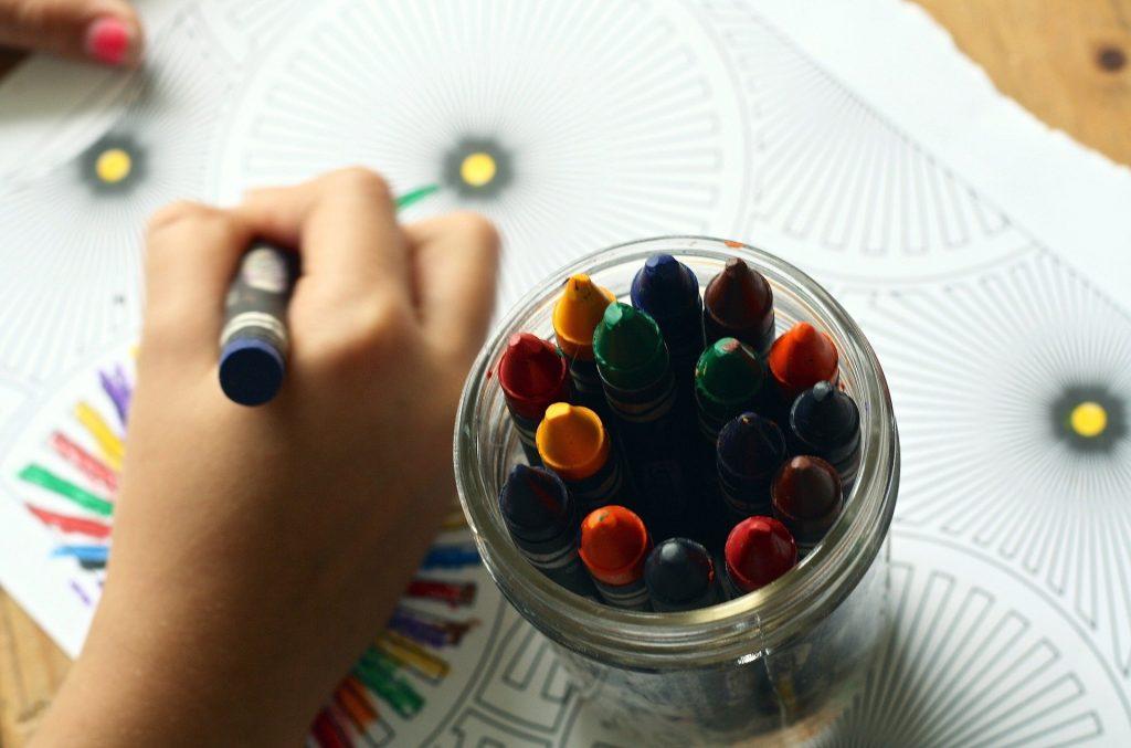 A mão de uma criança colore na alfabetização divertida com cores.