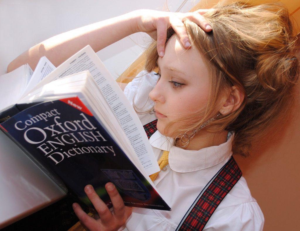 Uma menina adolescente estudando o Dicionário de Oxford, lembrando que o ensino de línguas não sofre com as mudanças no Ensino Médio.