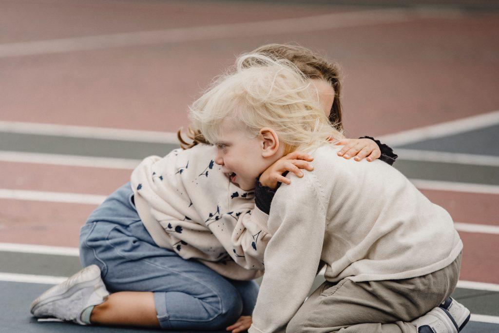 Duas crianças se abraçando no atendimento educacional.