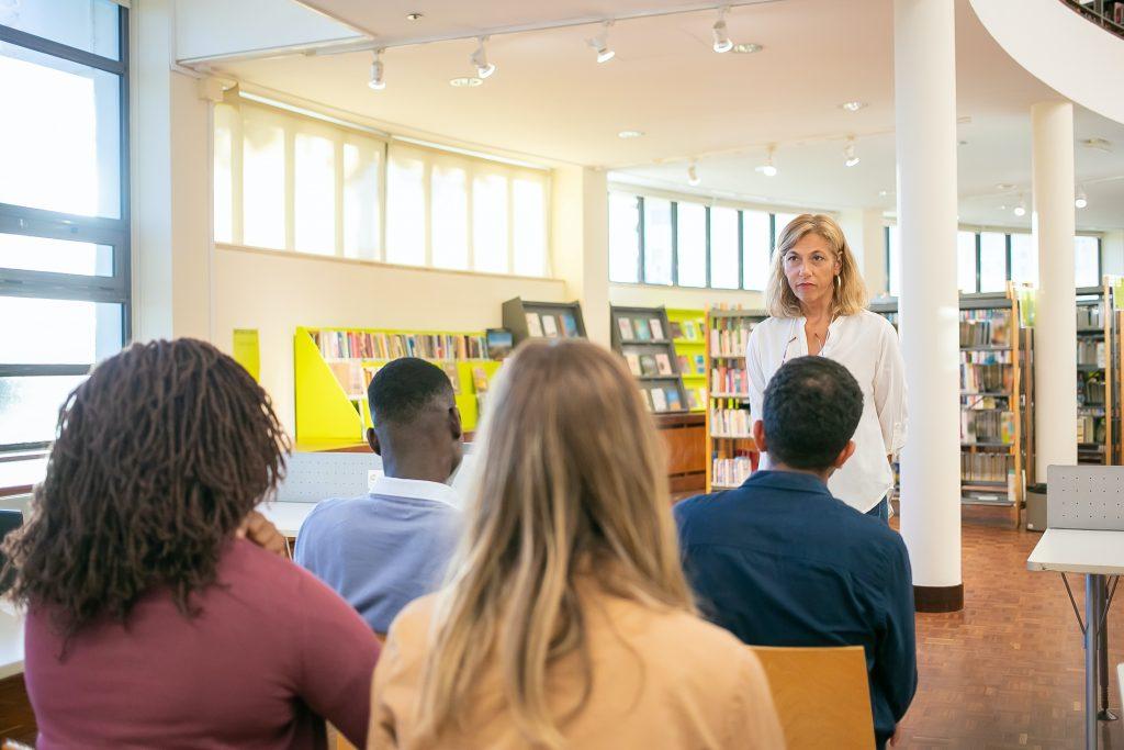 Professora em frente a uma sala de alunos que passaram pelas mudanças no Ensino Médio.