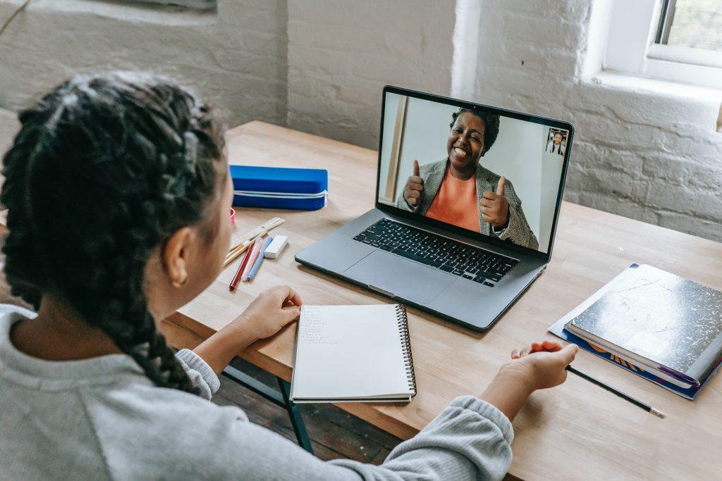 Uma menina tendo aula online na plataforma LMS e a professora na tela do computador apoiando os benefícios.