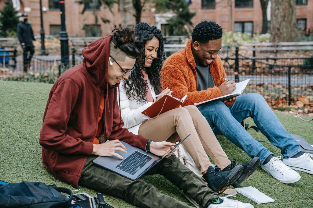 Três adolescentes (dois homens e uma mulher) estudando em livros e computador, adaptando-se às mudanças no Ensino Médio.
