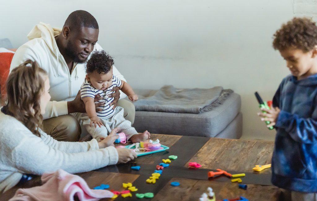 Homem e mulher brincando de alfabetização divertida com duas crianças.