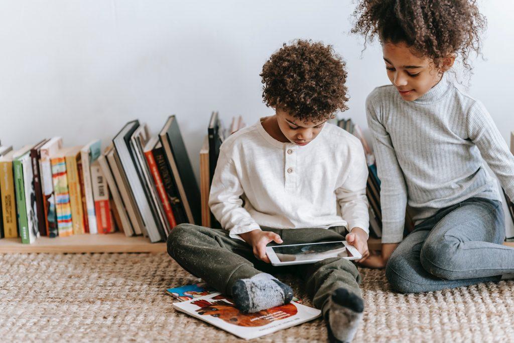 Um menino e uma menina em alfabetização divertida com tablet.