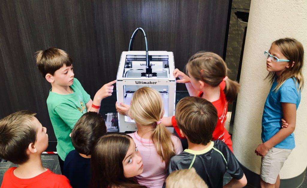 Grupo de oito crianças (4 meninas e 4 meninos) conversando sobre um equipamento, demonstrando a participação dos alunos nas aulas.