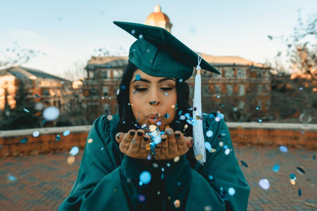 Uma menina adolescente vestida para a formatura (com toga e chapéu) assoprando confetes brilhantes comemorando a realização do Projeto de Vida com ajuda dos livros didáticos ensino médio.