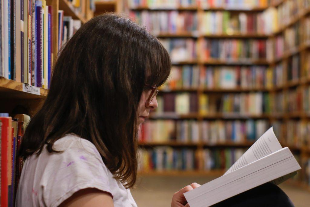 Uma menina adolescente estudando livro didático ensino médio na biblioteca.