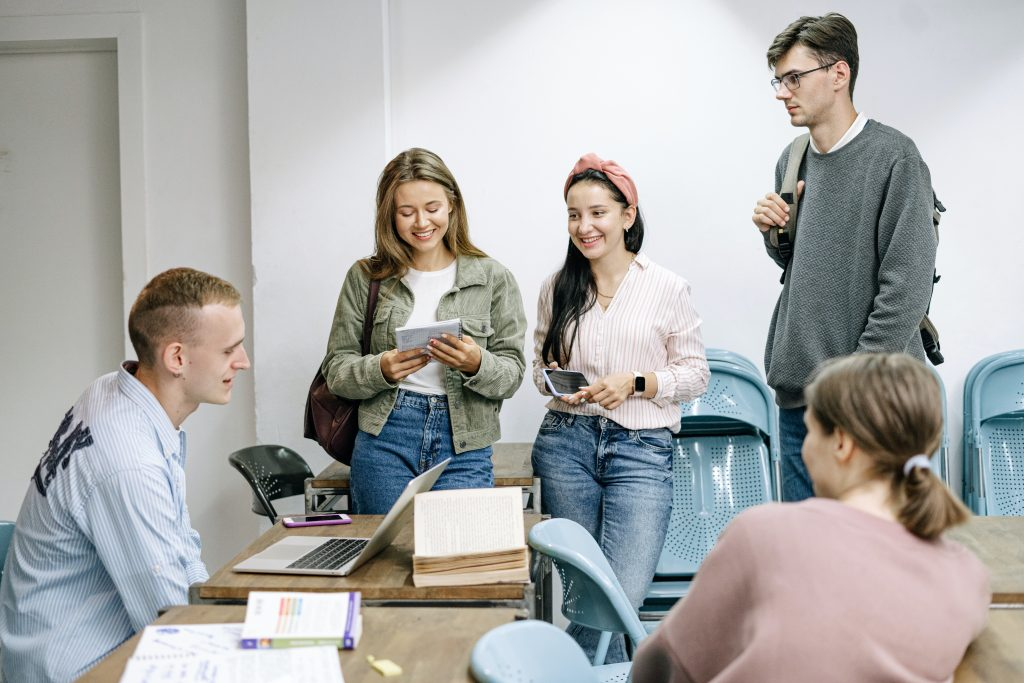 Cinco estudantes (três mulheres e dois homens) demonstrando a participação dos alunos nas aulas dentro da sala de forma descontraída.