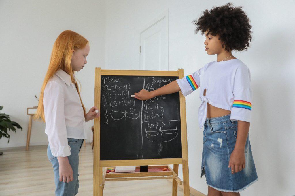 Duas meninas escrevendo em uma lousa demonstrando participação dos alunos nas aulas.