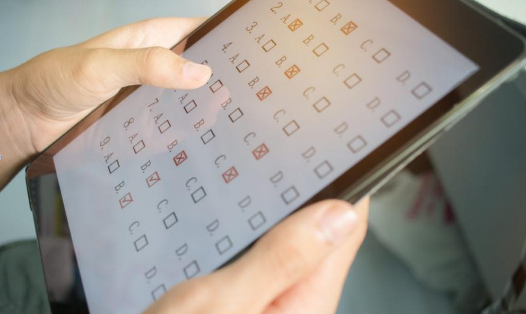 Aluno aproveitando as dicas para o ENEM digital, marcando as respostas em um tablet.