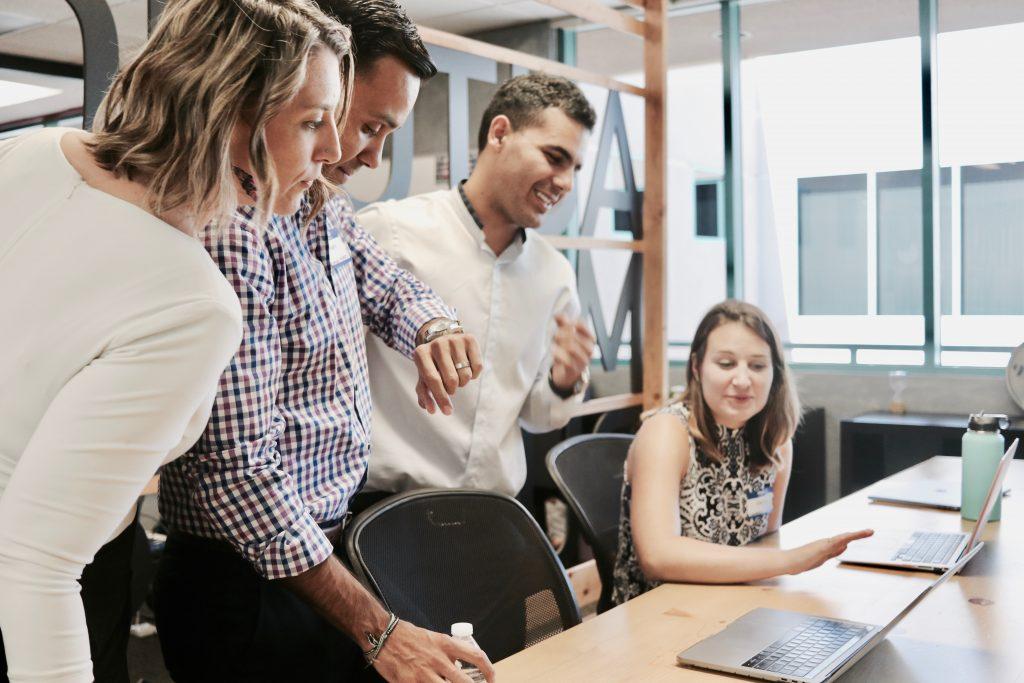 Equipe escolar reunida e economizando tempo de alinhamento com o uso de tecnologia de gestão