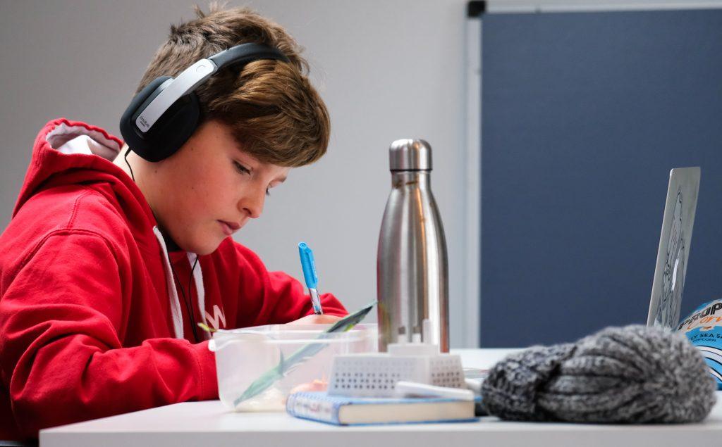 Aluno do Ensino Fundamental tendo aulas on-line no sistema de ensino híbrido no retorno aulas presenciais.