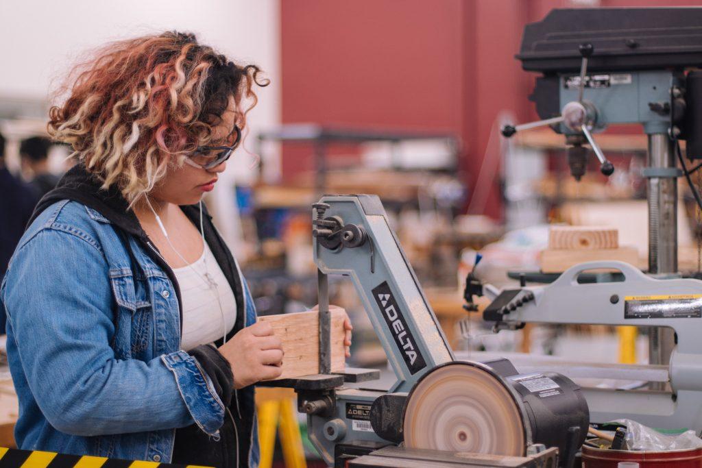 Aluna do ensino médio realizando atividade de carpintaria, como um exemplo de cultura maker na educação.