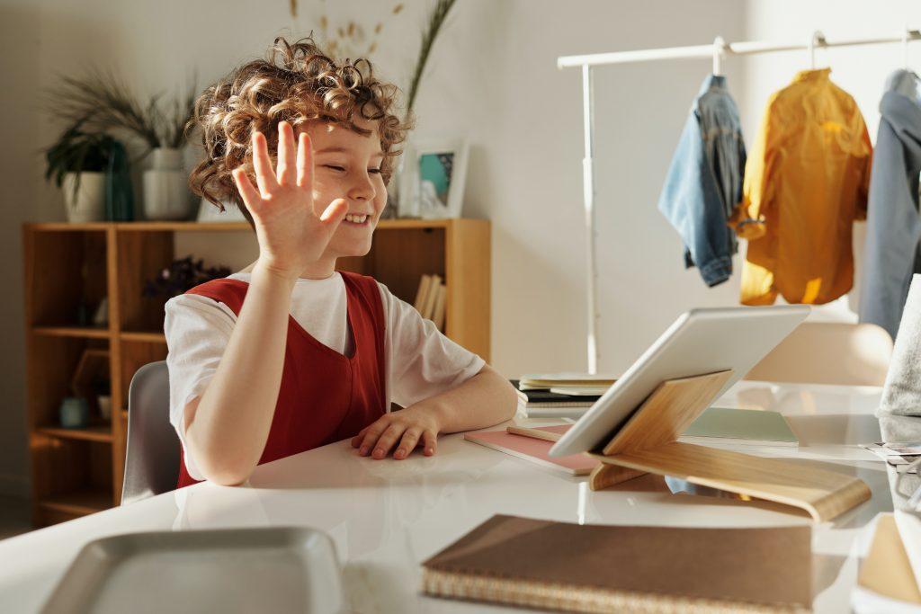 Uma criança fazendo aula online, usufruindo dos recursos de tecnologia de gestão.