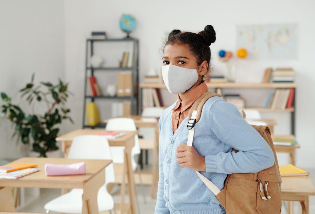 Aluna do Ensino Fundamental de máscara e mochila no retorno aulas presenciais.