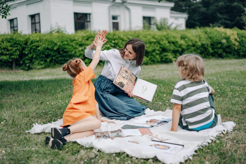 Professoras e dois alunos do Ensino Fundamental (uma menina e um menino) tendo aulas na grama, área externa da escola, no retorno aulas presencias.
