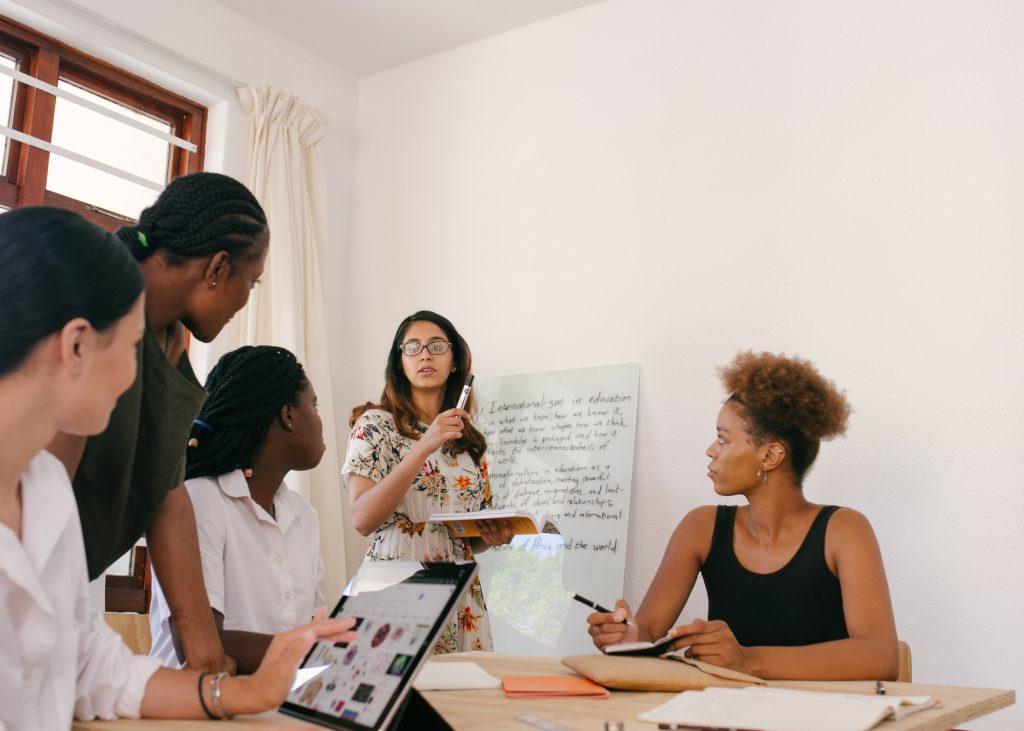 Cinco mulheres diversas em reunião sobre a tecnologia de gestão na escola. Uma, mais a frente, toma nota em um tablet, outra, mais ao fundo, escreve em um quadro branco.
