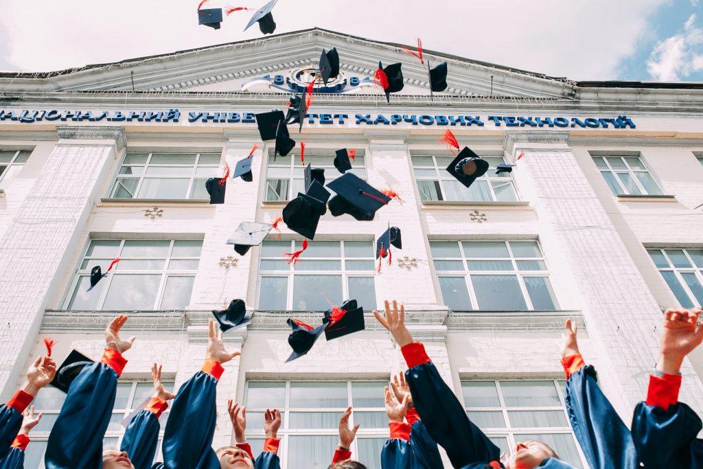 Alunos do Ensino Médio jogando o chapéu de formatura para cima em comemoração do sucesso acadêmico atrelado à cultura maker na educação.