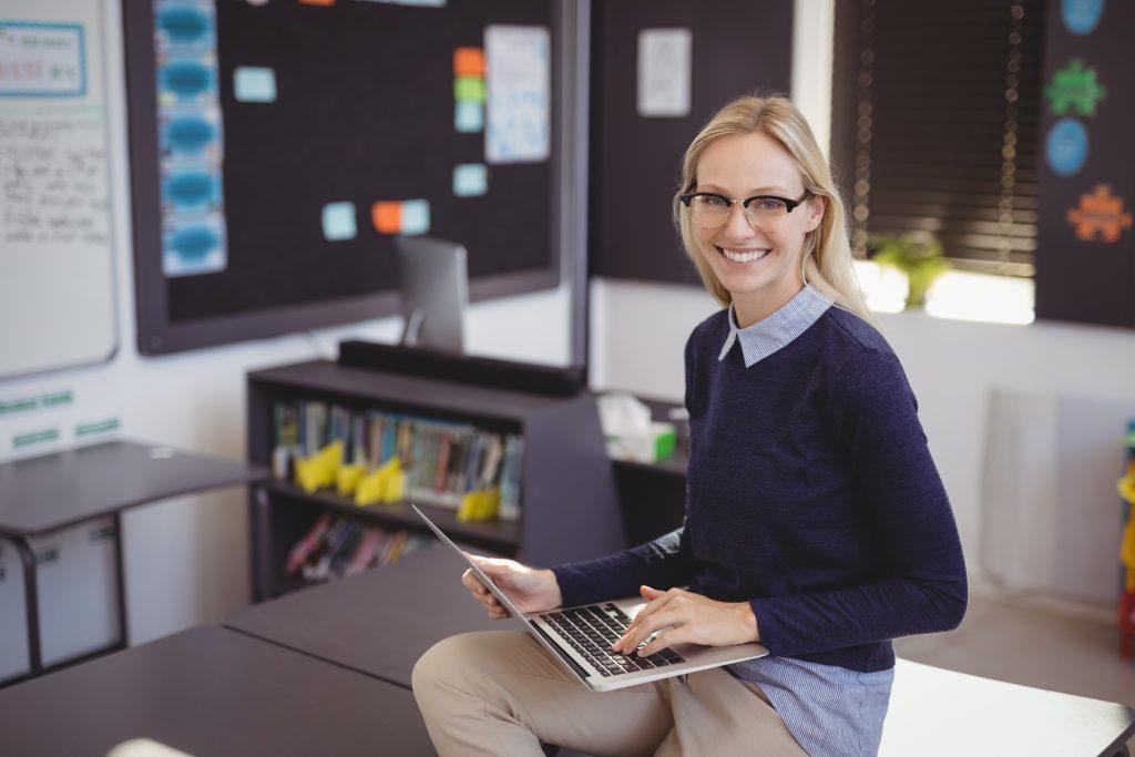 Na imagem temos uma mulher de óculos ao telefone, sentada na frente do computador, utilizando a plataforma adaptativa para fazer a gestão escolar.