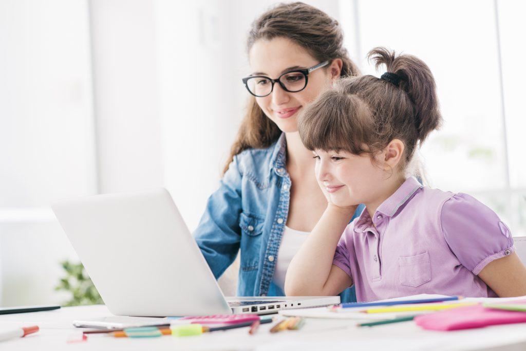Irmã mais velha e irmã mais nova trabalhando juntas nas atividades da plataforma de ensino digital em outro exemplo de temas para trabalhar com famílias.