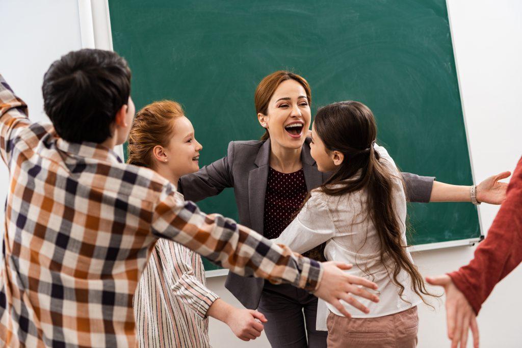 Professora e alunos dando um abraço com distânciamento social para praticar as habilidades socioemocionais com segurança.