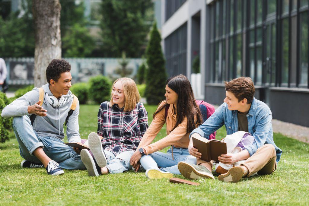 Adolescentes (dois homens e duas mulheres) conversando no gramado da escola e colocando em prática o acolhimento e as habilidades socioemocionais.