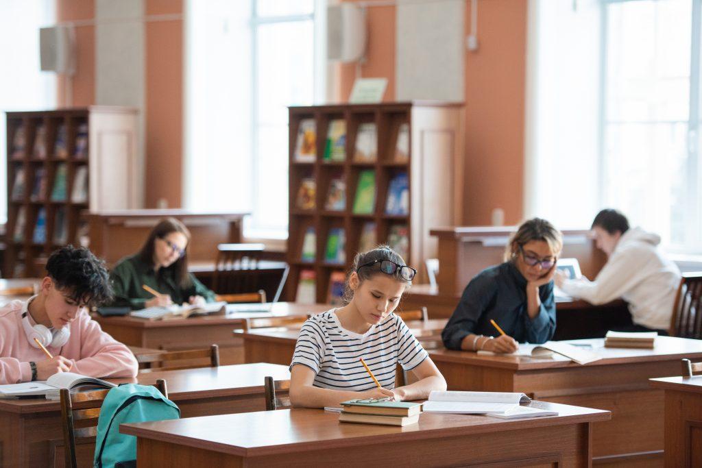 Adolescentes em sala de aula realizando simulados Enem.