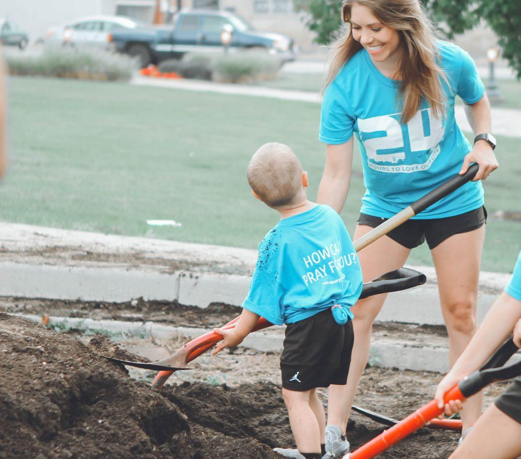 Mulher e criança cavando a terra junto e colocando em prática os temas para trabalhar com famílias.