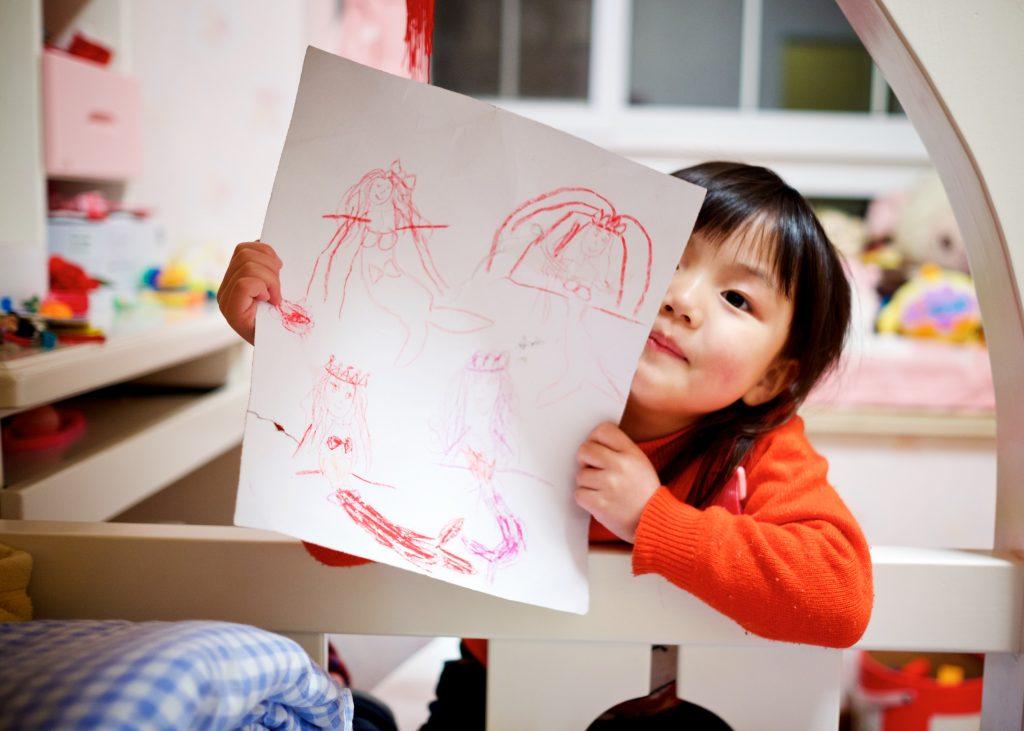 Uma criança mostrando o desenho que fez sobre seus sentimentos na atividade proposta para trabalhar as habilidades socioemocionais.