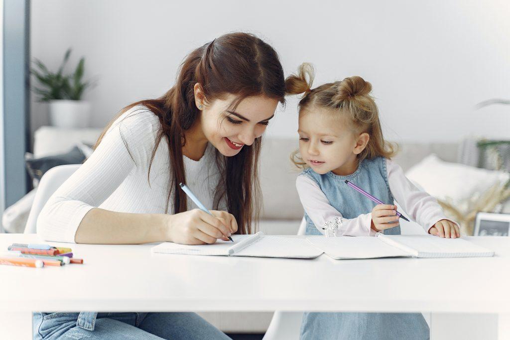 Mãe e filha fazendo a atividade de casa juntas e praticando as habilidades socioemocionais.
