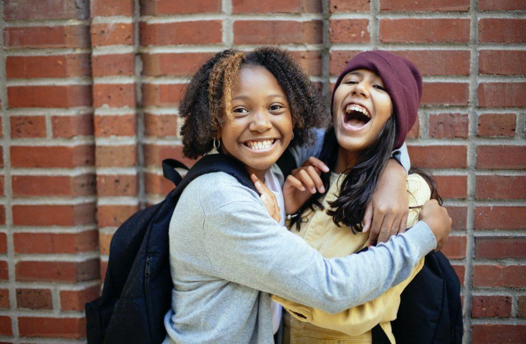 Duas meninas sorrindo e se abraçando em acolhimento mutuo, demonstrando porque é importante trazer temas para trabalhar com famílias.