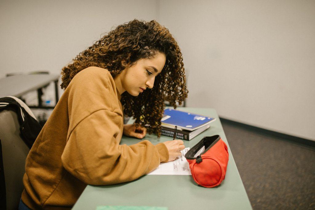 Mulher adolescente de cabeço longo e cacheado fazendo Simulados Enem na escola.
